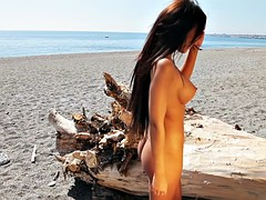 Ridiculously hot brunette chick posing on the beach
