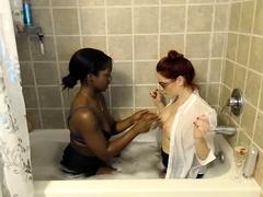 Interracial lesbian friends kiss each other in the bathtub